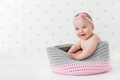 Cute baby sitting happy and laughing in a woollen basket. - PhotoDune Item for Sale