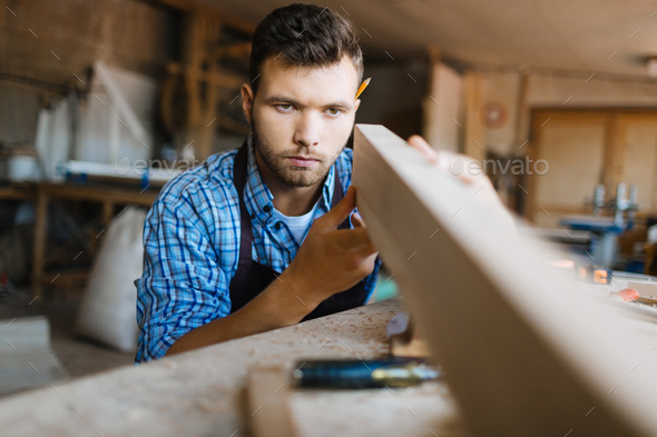 Checking straightness of plank - Stock Photo - Images