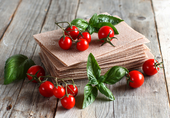 Raw lasagna sheets and cherry tomatoes - Stock Photo - Images