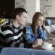 Boy And Girl In Cafe. People Use Laptop And Smartphones, Talk And Drink Coffee. - VideoHive Item for Sale