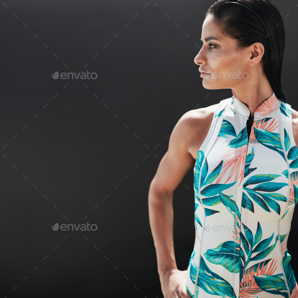 Beautiful young woman standing against black background - Stock Photo - Images