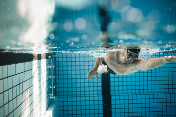 Fit young male swimmer training in the pool