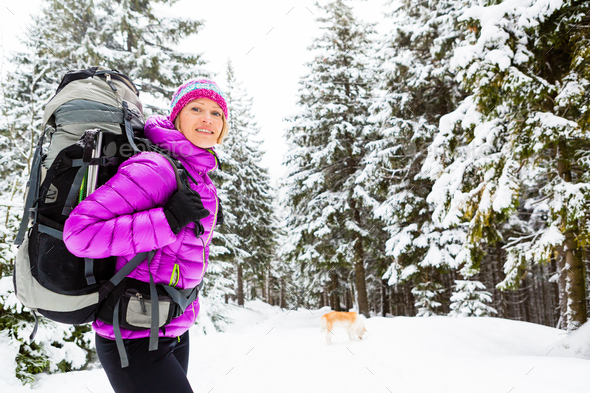 Happy woman walking in winter forest with dog - Stock Photo - Images