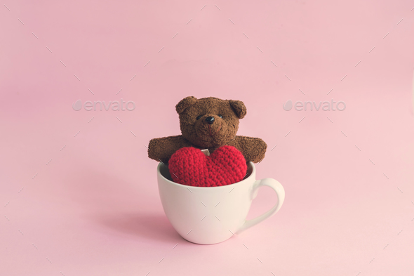 Teddy bear with red heart shape in cup of coffee - Stock Photo - Images