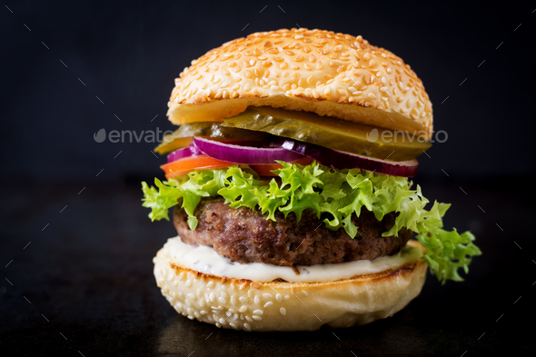 Big sandwich - hamburger burger with beef, pickles, tomato and tartar sauce on black background. - Stock Photo - Images