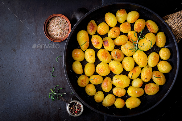 Baked potatoes with rosemary and pepper in a frying pan on black background. Top view - Stock Photo - Images