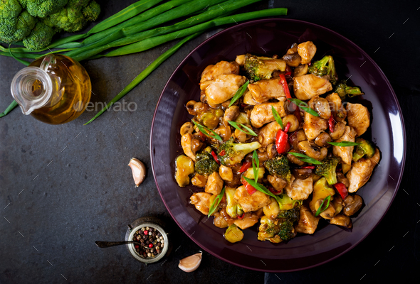 Stir fry with chicken, mushrooms, broccoli and peppers - Chinese food. Top view - Stock Photo - Images