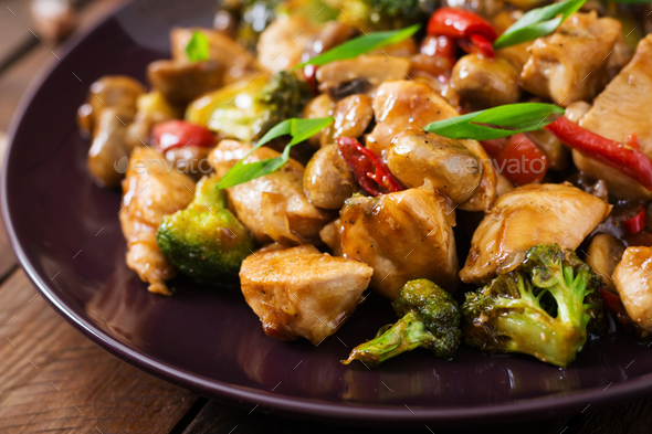 Stir fry with chicken, mushrooms, broccoli and peppers - Chinese food - Stock Photo - Images