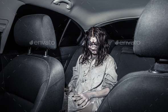 Horror zombie woman with bloody face in the car - Stock Photo - Images