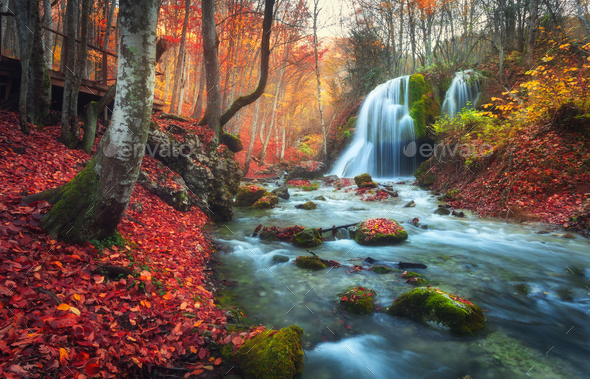 Autumn forest with waterfall at mountain river at sunset - Stock Photo - Images