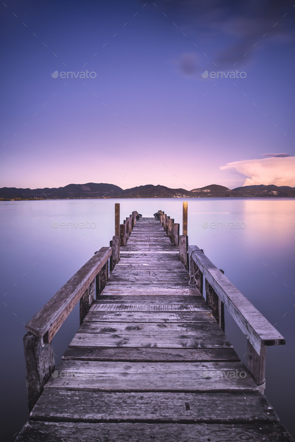 Wooden pier or jetty on a blue lake sunset and sky reflection on - Stock Photo - Images