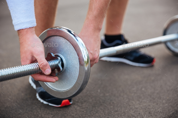 Muscular fitness man going to lift heavy barbell - Stock Photo - Images