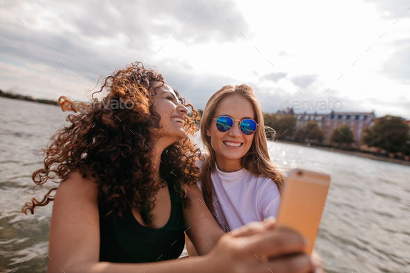 Beautiful young women taking selfie by the lake - Stock Photo - Images