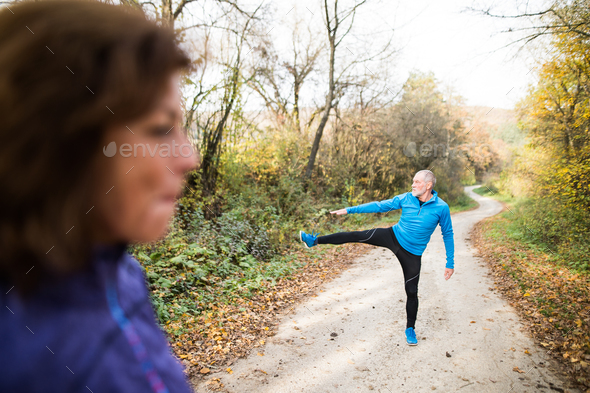 Senior couple running outside in sunny autumn forest, stretching - Stock Photo - Images