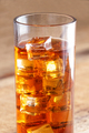a glass of ice tea with many ice cubes