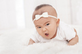cute baby girl lying on fur blanket with angry expression - PhotoDune Item for Sale
