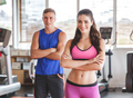 sporty woman and man with armcrossed at the gym
