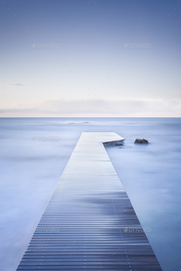 Wooden pier, rocks and calm sea on long exposure. - Stock Photo - Images