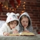Two Little Cute Siblings Reading a Book In Bed Near Christmas Tree With Lights And Illumination - VideoHive Item for Sale