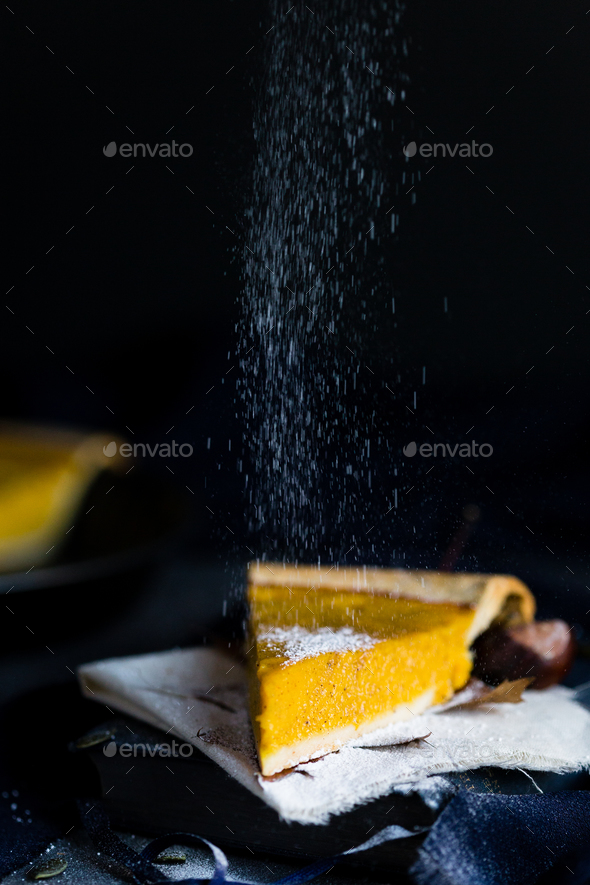 Sprinkling Icing Sugar on a Slice of Pumpkin Pie - Stock Photo - Images
