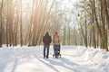 parents carry the baby in a stroller through the snow - PhotoDune Item for Sale
