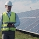 Solar Panel Technician Using Tablet Near Array