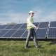 Man In Hard Hat Walking Past Solar Panels - VideoHive Item for Sale