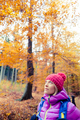 Hiking woman with backpack looking up at inspiring autumn trees