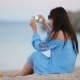 Young Woman Take a Picture On Phone On The Beach At The Evening - VideoHive Item for Sale