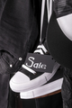 Close up of hanging black and white sneakers with sign Sale near jeans  cap on  background. Friday .