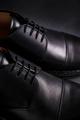 Black oxford shoes on  background. Back view. Close up.