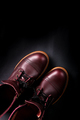 Fashionable mens leather brown shoes on black background. . Men's high boots. Top view. Copy space.
