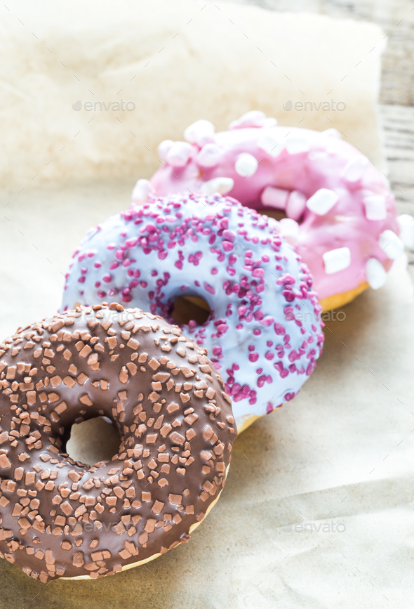 Colourful donuts on the baking paper - Stock Photo - Images