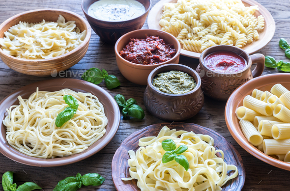 Pasta with different kinds of sauce on the wooden background - Stock Photo - Images