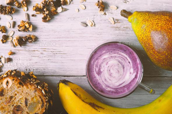 Berry farm yogurt in a jar, granola, banana, bread loaf - Stock Photo - Images
