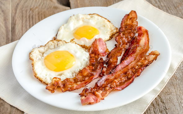 Fried eggs with bacon on the wooden table - Stock Photo - Images