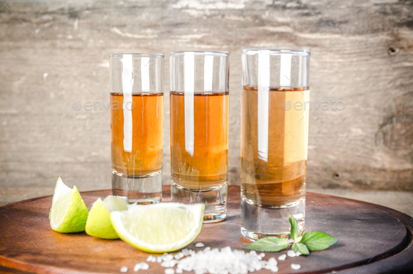Glasses of tequila on the wooden board - Stock Photo - Images