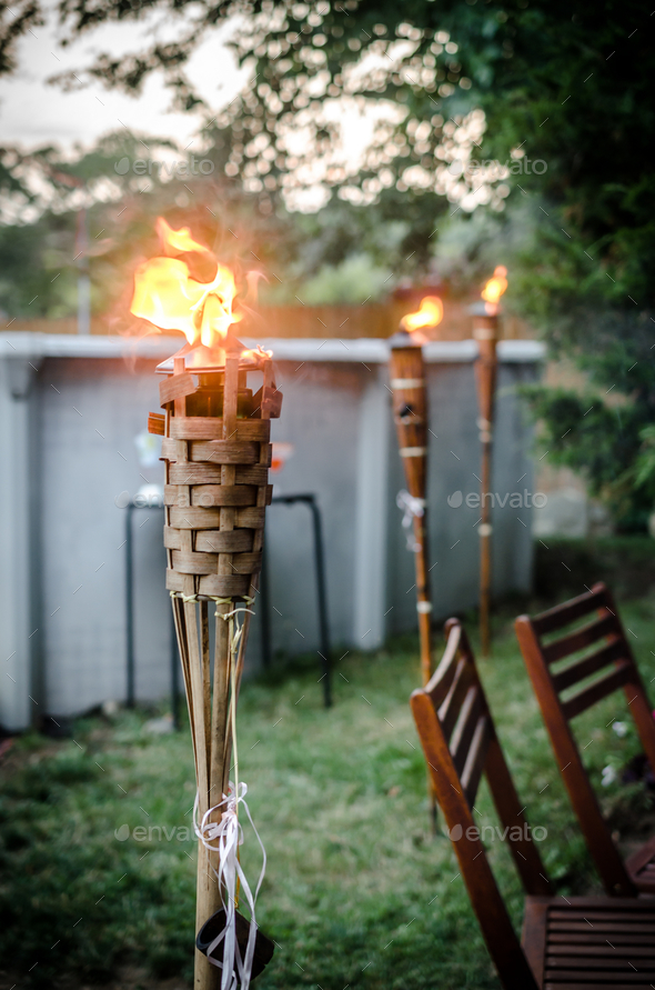 Burning tiki torch in the backyard - Stock Photo - Images