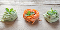 Colorful rolled pasta on the wooden background