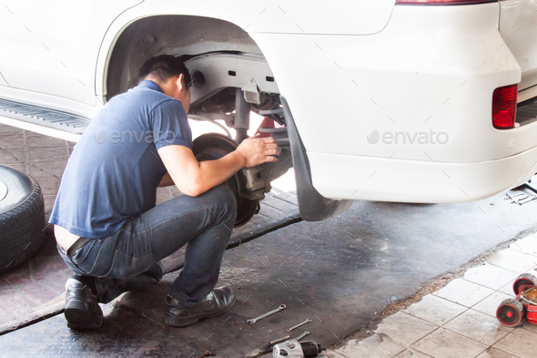 Mechanic inspecting the suspension and brakes of car at workshop - Stock Photo - Images