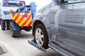 Tow truck towing a broken down car on the street - PhotoDune Item for Sale
