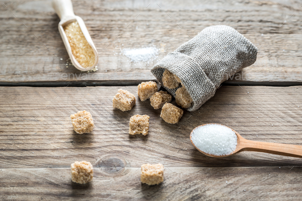 Brown and white sugar on the wooden background - Stock Photo - Images