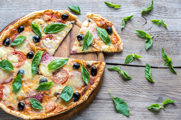 Cut pizza on the wooden board - Stock Photo - Images