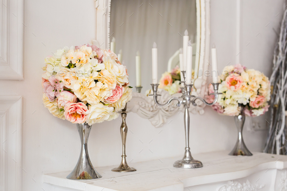 Bouquet on a fireplace with candle holders in a beautiful interior. - Stock Photo - Images