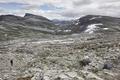 Norwegian rocky mountain landscape with snow and hiker. Norway trekking. Horizontal