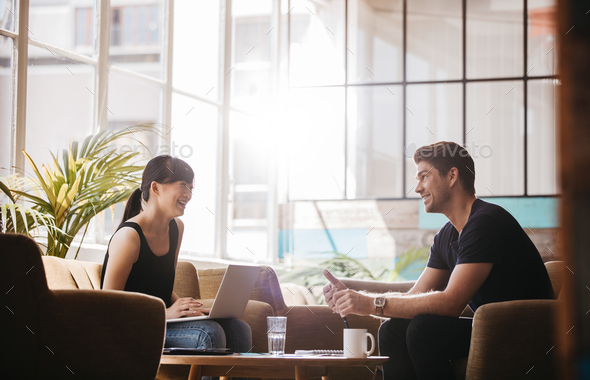 Smiling business partners working together in modern office - Stock Photo - Images