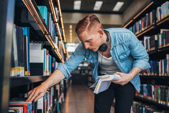 Student looking for a book in shelf - Stock Photo - Images