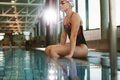 Sporty fit woman relaxing at swimming pool edge