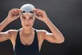 Female swimmer posing on black background