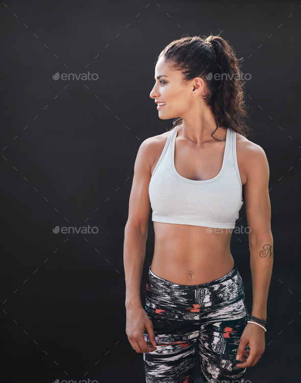 Sportswoman with muscular body on black background - Stock Photo - Images